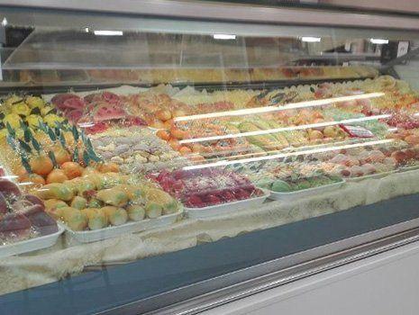 esposizione di dolci canditi e frutta dietro a un vetro
