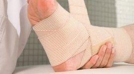 Medico benda la caviglia di un paziente