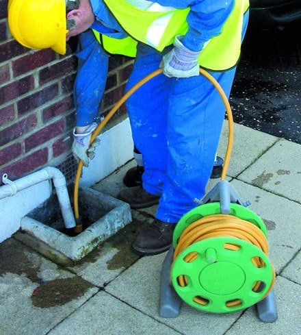 A expert cleaning a domestic drain