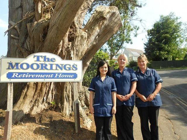 The Moorings Retirement Home staff next to the home road sign