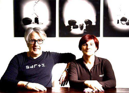 foto con un unomo e una donna in primo piano dietro una scrivania
