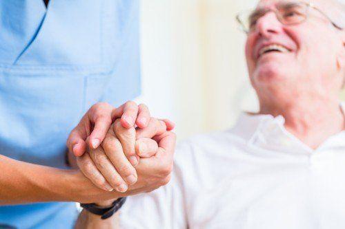 Un infermiera che regge la mano ad un anziano