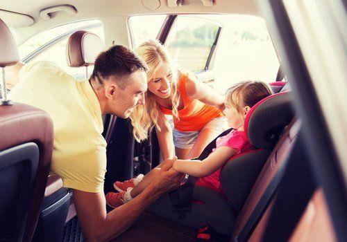 famiglia in macchina con bambina sul seggiolino