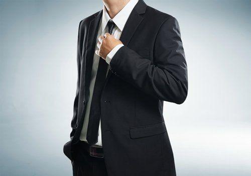 uomo in abito formale che si sistema la cravatta