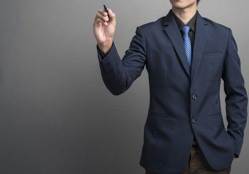 Uomo con la mano in tasca, vestito in giacca e cravatta, che regge una biro in mano