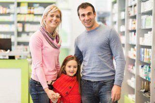 famiglia composta da padre madre e figlioletta in una farmacia