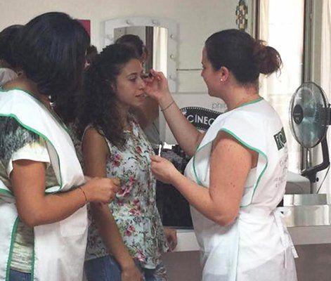 un'estetista con un grembiule bianco sta truccando una ragazza con capelli ricci neri e accanto un'altra ragazza sta guardando