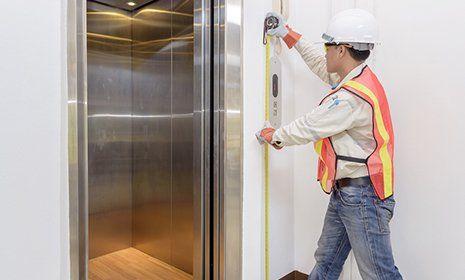 Un tecnico misura un'ascensore con un metro