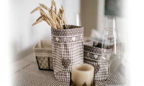 una candela e dei porta pane ricoperti in stoffa