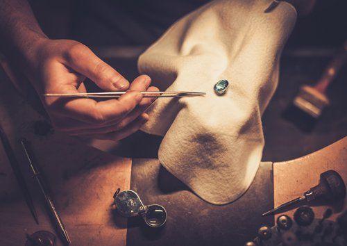Gioielliere analizza una pietra preziosa tenendola su un panno