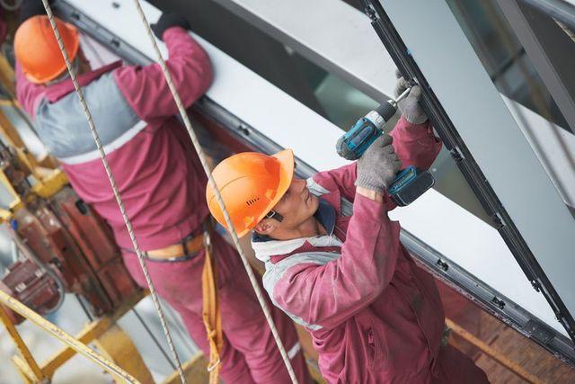 due uomini con uniforme bordeaux ed elmetto arancione stanno lavorando su dei pannelli in ferro