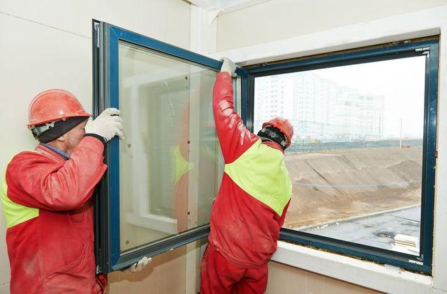 due operai con uniforme rossa e verde fosforescente con degli elmetti rossi stanno posizionando una finestra in vetro e pvc