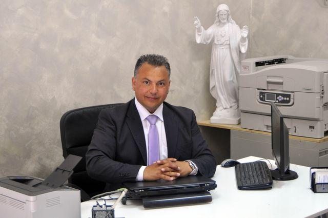 uomo con giacca nera alla scrivania bianca