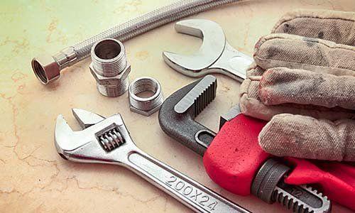 una chiave inglese, un pappagallo, dei bulloni e un paio di guanti da lavoro