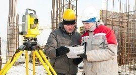 due tecnici consultano un foglio con accanto un impianto di misurazione sismico