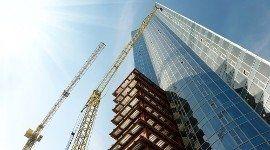 vista dal basso di due gru e di un grattacielo