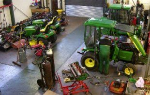 Our workshop with man fixing large mower