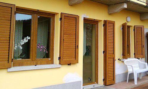 delle persiane in legno su delle finestre all'esterno di una casa