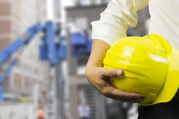 professionista con in mano un caschetto per la sicurezza sul lavoro