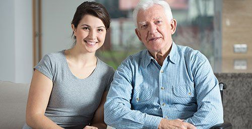 Caretaker and elderly patient are smiling