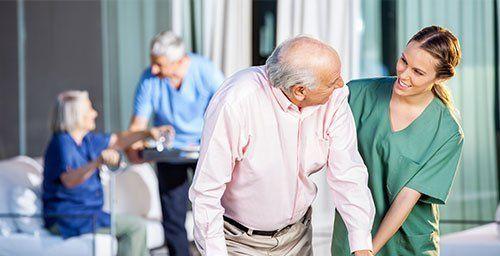 Caretaker assisting senior man in using zimmer frame