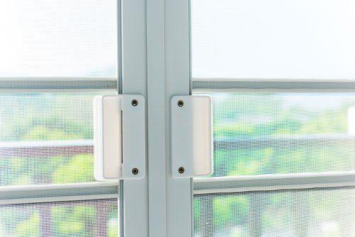 vista ravvicinata di una finestra con rifinitura in pvc e delle zanzariere tese