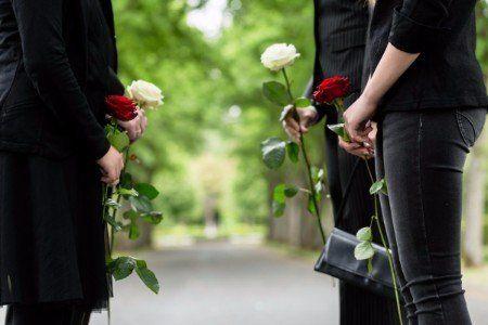 Due donne con rosa rossa e due uomini con rosa bianca fanno corridoio nel cimitero