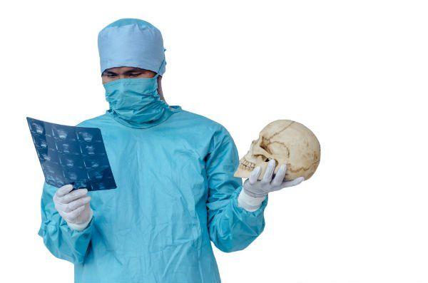 un dottore con una tuta protettiva, una mascherina e in mano una lastra e un teschio