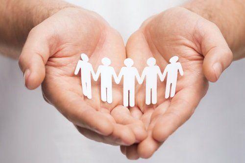 Mani in forma di cuore sostenendo una famiglia