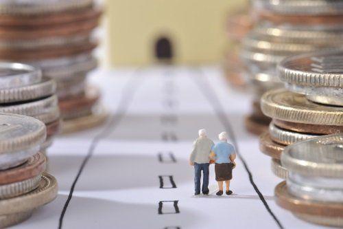 Anziani camminando verso un tunnel tra pile di monete
