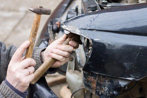 carrozziere che lavora su un'auto incidentata