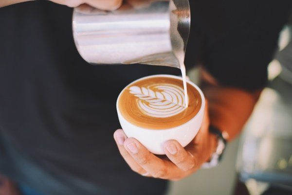 uomo versando il latte nel cappuccino