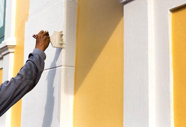 mano di un uomo che dipinge un muro