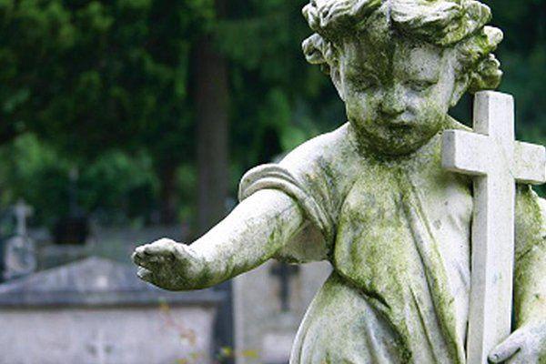 una statua di un angelo con una croce in mano