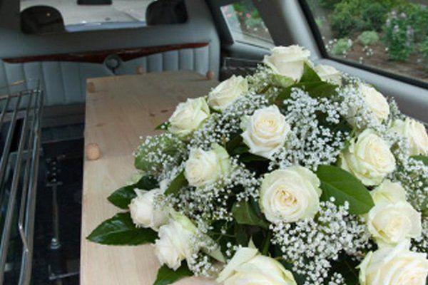 un bouquet di rose bianche su una bara in un carro funebre