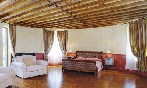 una camera da letto con delle poltrone, un letto e un pavimento in parquet