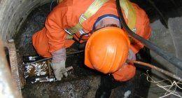 un uomo con una tuta e un elmetto al lavoro in un pozzo nero