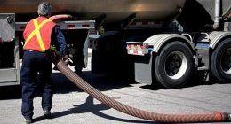 un uomo con una pettorina rossa e un tubo vicino a un camion degli spurghi