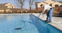 un uomo pulisce una piscina