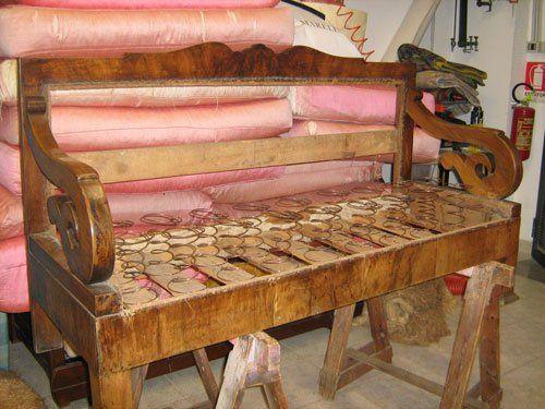 Una struttura in legno di un divano con vista delle molle sulle doghe