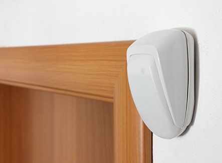 An alarm point mounted on an interior wall above a door