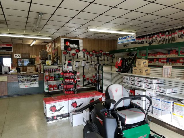 Showcase of the new powerful red gasoline lawn mower in the store (shop). Indoor shoot with nobody