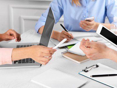 documenti, tablet e penne in una scrivania di colleghi