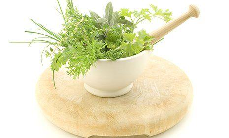 una ciotola di porcellana di color bianco appoggiata su un tagliere rotondo di legno chiaro con dentro delle erbe e un piccolo mattarello