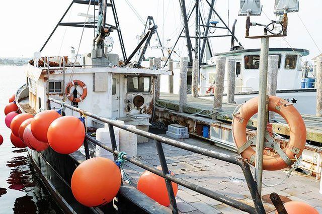 vista laterale di un peschereccio con salvagenti e boe arancioni sui lati
