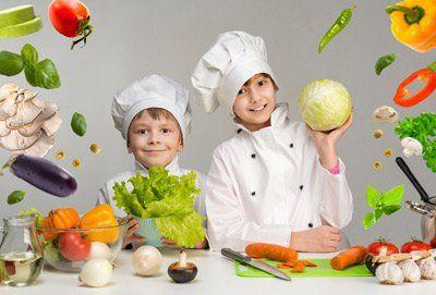 due bambini mentre giocano a fare i cuochi