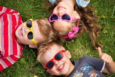 tre bambini sdraiaiti sull`erba