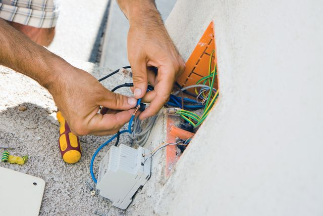 close up of electrician's hands working on some wires