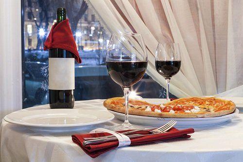 Tavola per due, pizza, due bicchieri di vino rosso, bottiglia di vino aperta, coperti, cortina aperta