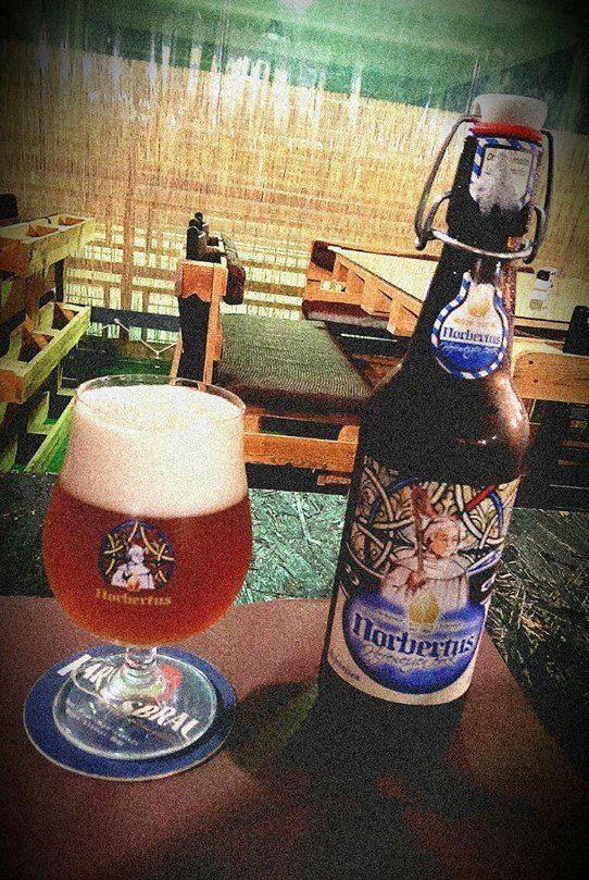 una bottiglia e un bicchiere di birra sul bancone di una birreria